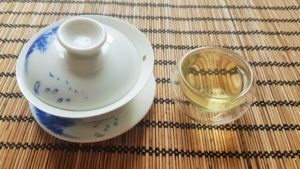 Glass tea cup with Lung Ching tea in it and Gaiwan beside it.