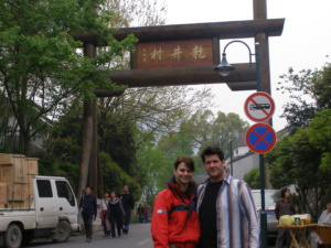 The owners of teahouse emporium infront of the Lung Ching village sign