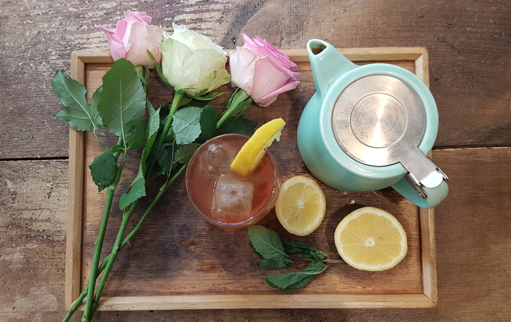 rose earl grey iced teas on a tray with a teapot and roses